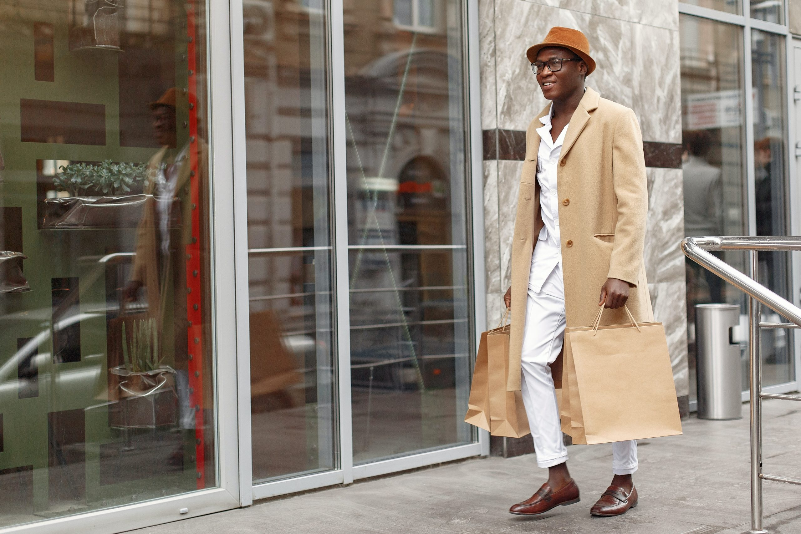Man walking in beige pea coat with two shopping bags