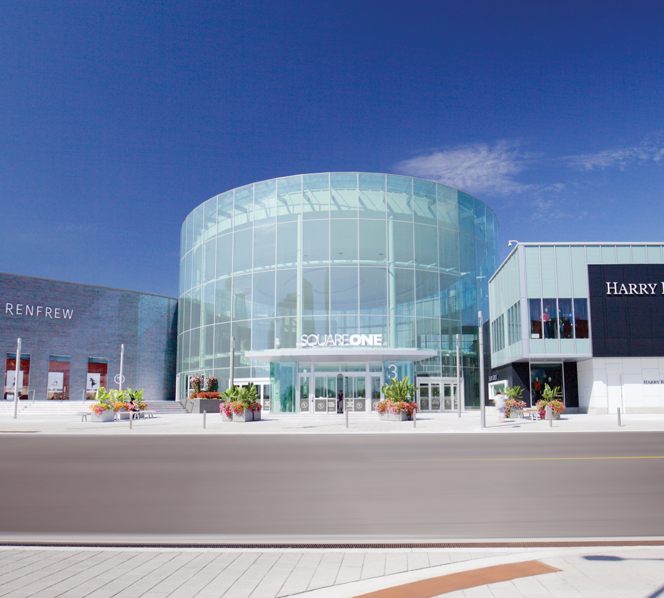 Exterior glass round entrance of Square One shopping centre summer time with bright blue sky.
