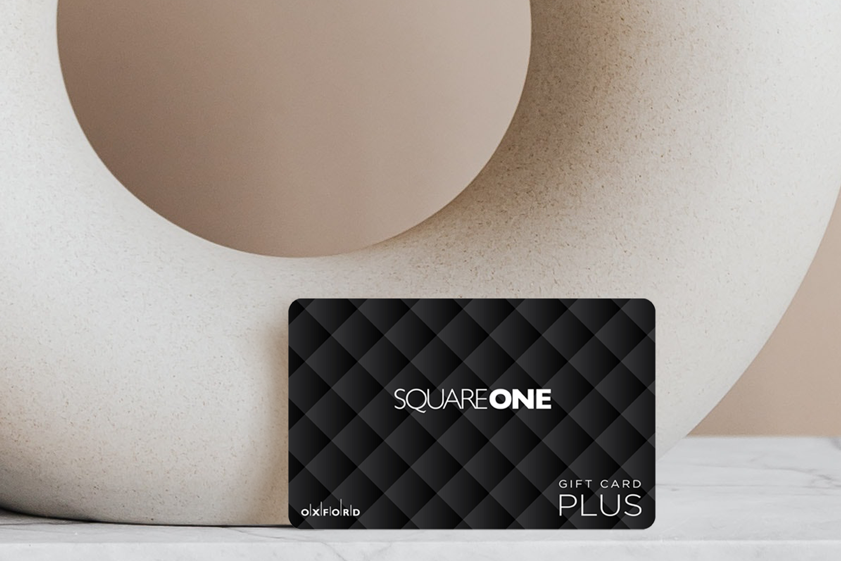 Square One black quilted gift card leaning against beige circular vase.