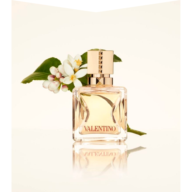 Perfume bottle with flowers behind.