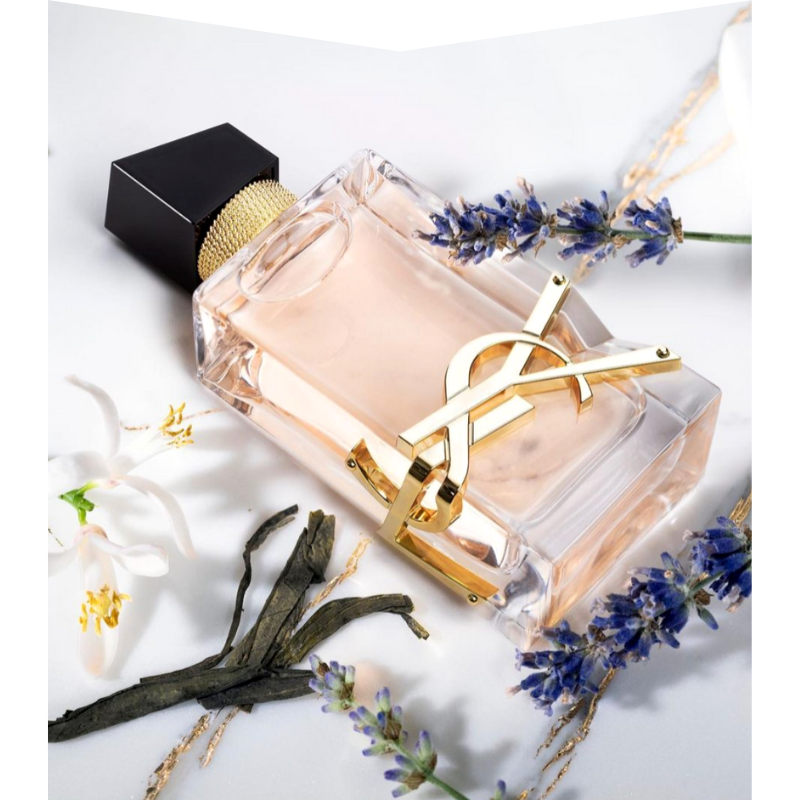 Perfume bottle with flowers surrounding it.